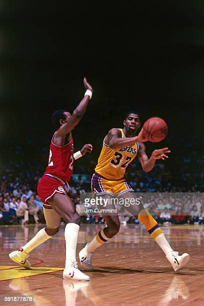 Magic Johnson of the Los Angeles Lakers passes the ball against the Philadelphia 76ers on November 26, 1996 at the Great Western Forum in Inglewood,...