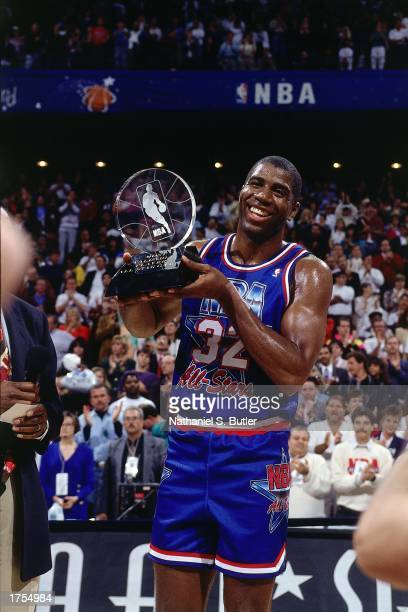 Magic Johnson of the Los Angeles Lakers poses with the AllStar MVP Trophy during the 1992 NBA AllStar Game at the Orlando Arena on February 9 1992 in...