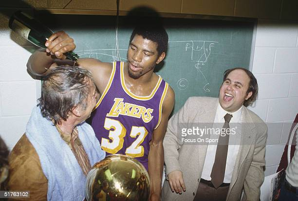 Magic Johnson of the Los Angeles Lakers pours a bottle of champagne over the owner of the Lakers Jerry Buss after winning Game 6 of the 1980 finals...