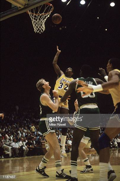Magic Johnson of the Los Angeles Lakers rebounds over Larry Bird of the Boston Celtics during an NBA Finals game at the Great Western Forum in Los...