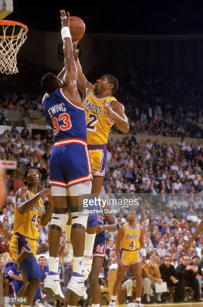 Magic Johnson of the Los Angeles Lakers shoots a lay up over Patrick Ewing of the New York Knicks during an NBA game at the Great Western Forum in...