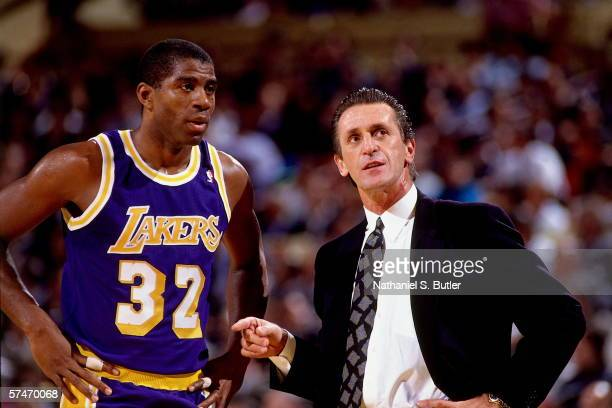 Magic Johnson of the Los Angeles Lakers talks with head coach Pat Riley during a game against the New York Knicks circa 1990 at Madison Square Garden...