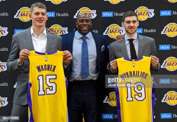 Magic Johnson the Los Angeles Lakers president of basketball operations stands with the team's 2018 NBA draft picks Moritz Wagner and Sviatoslav...