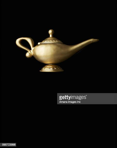 magic lamp against black background - lampara de aladino fotografías e imágenes de stock