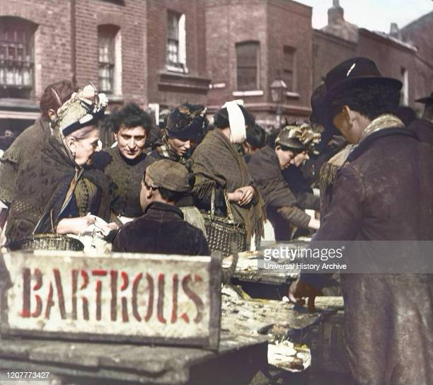 Magic lantern slide circa 1880, Victorian/Edwardian Social History. A fishmonger stall in the market with lots of people buying fish, including...
