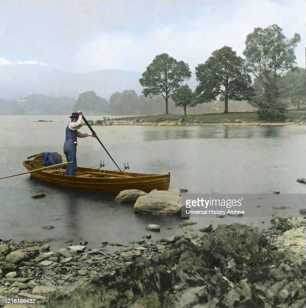 Magic Lantern slide circa 1880, Victorian/Edwardian, social history. A man punting a rowing boat on Lake Windermere; Cumbria, England.