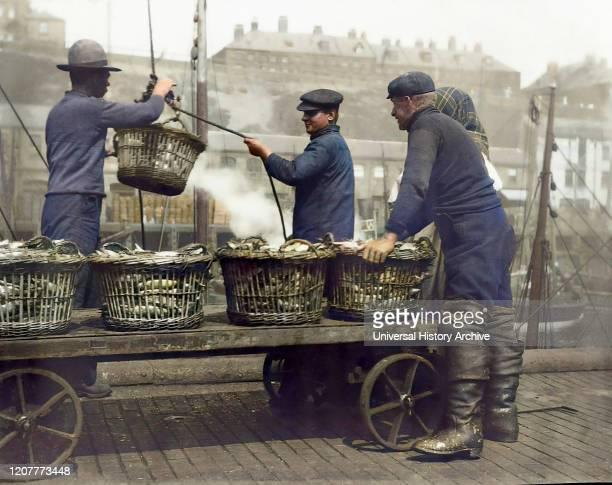 Magic lantern slide circa 1880., Victorian/Edwardian Social History. Landing Herring at North Shields Fish Quay. Three fishermen with baskets and...