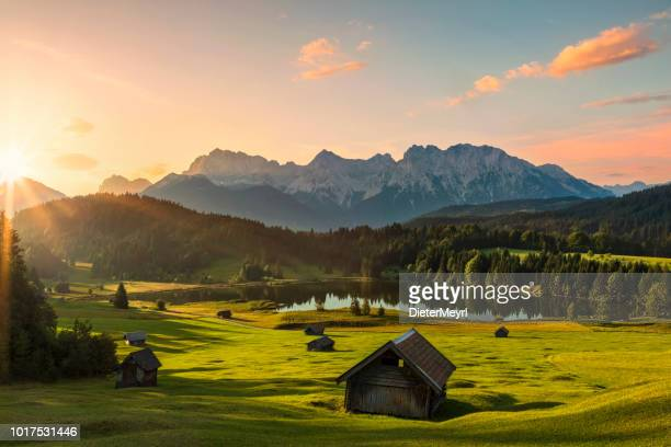 magic sunrise at alpine lake geroldsee - view to mount karwendel, garmisch partenkirchen, alps - landscape scenery stock photos and pictures
