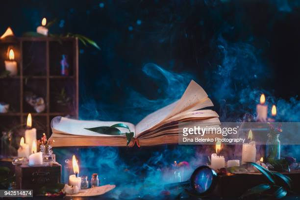 magical book of spells flying above wizard workplace with candles, herbs and a magnifying glass. dark fantasy still life with copy space. - rechtschreibung stock-fotos und bilder
