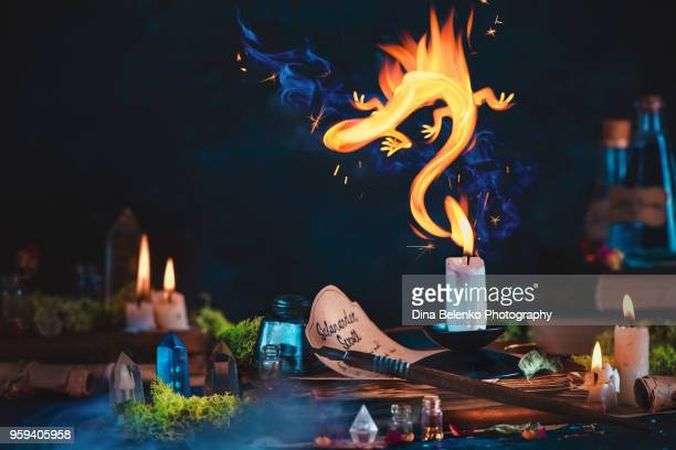 Magical fire Salamande from candle flame in a fairy tale still life with a witch or wizard workplace, occult crystals, moss, spell scrolls, potions, and herbs. Dark concept with copy space