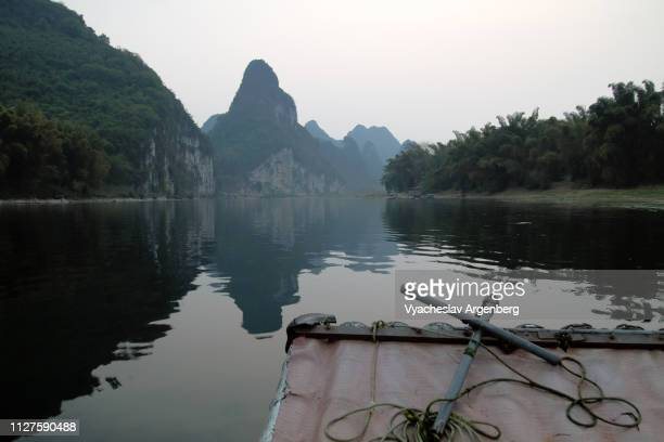 magical late evening atmosphere on li river east of yangshuo, karst peaks and their reflections on water during blue hour - argenberg ストックフォトと画像