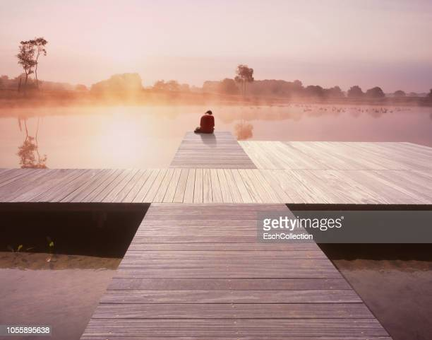 Magical sunrise at misty lake with woman sitting at end of a jetty