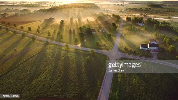 magical sunrise through ground fog with long shadows and sunbeams - zonnestraal stockfoto's en -beelden
