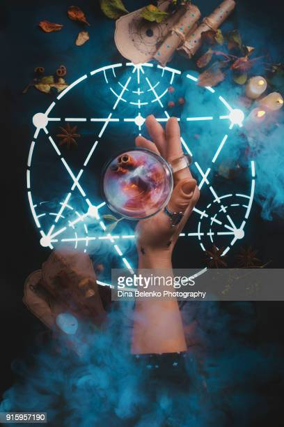 Magical tea in young witch hand in the center of a glowing alchemical pentagram. Dark still life with a hot beverage. Conceptual food photography.