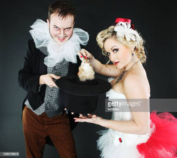 magician and assistant pulling a bunny out of hat - elizabethan collar stock photos and pictures