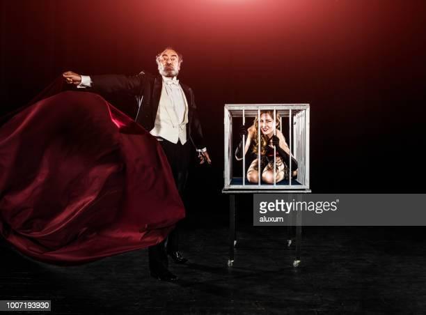 ステージ上でマジシャンのトリック パフォーマンスのケージの中に表示される魔術師アシスタント - 登場 ストックフォトと画像