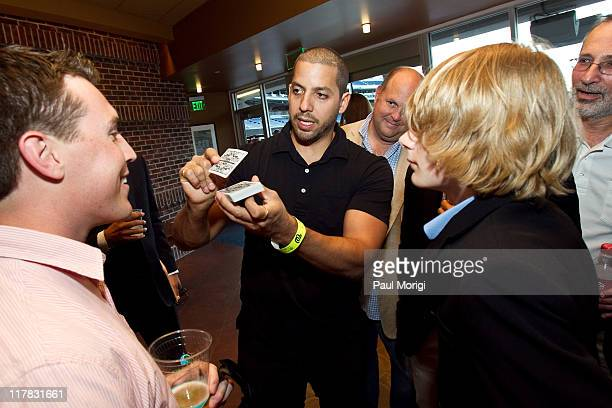 Magician David Blaine shows a card trick to guests at Ryan Zimmerman's 2nd Annual 'A Night At The Park' at Nationals Park on June 30 2011 in...