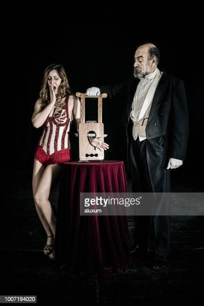magicien faire truc de guillotine avec assistant sur scène - guillotine photos et images de collection