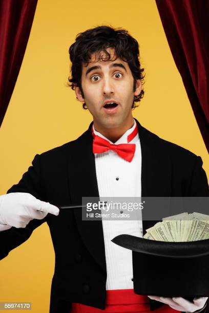 Magician holding top hat full of money