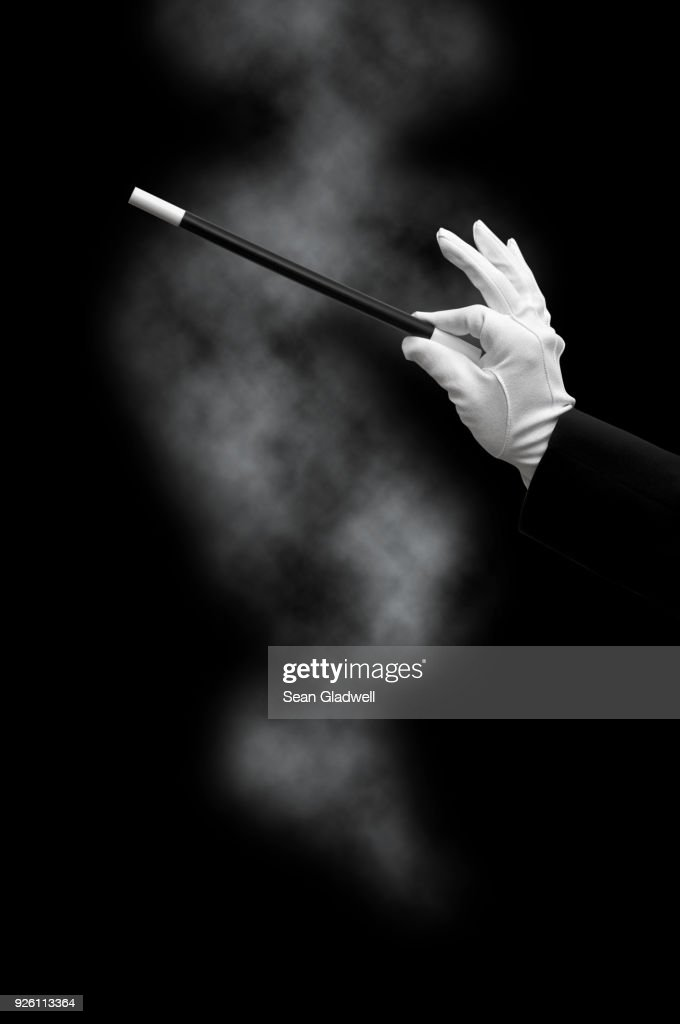 Magician holding wand with smoke : Stock Photo