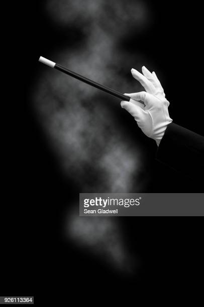 magician holding wand with smoke - white glove stock pictures, royalty-free photos & images