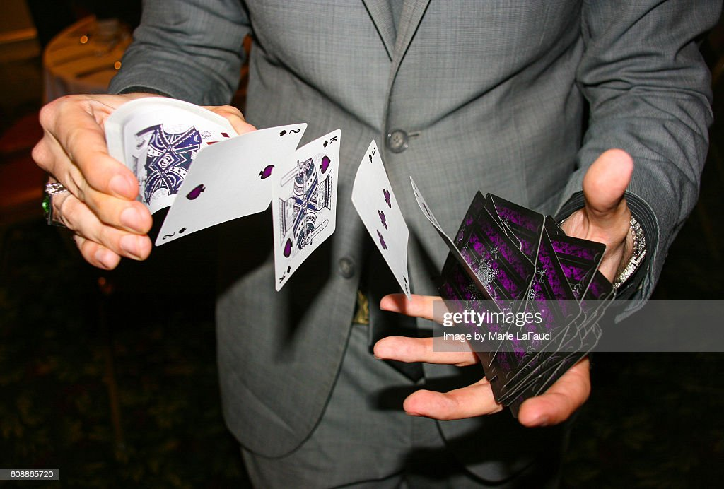 Magician illusionist performing card trick : Stock Photo