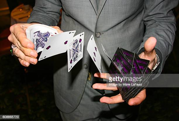 magician illusionist performing card trick - hoeren stockfoto's en -beelden