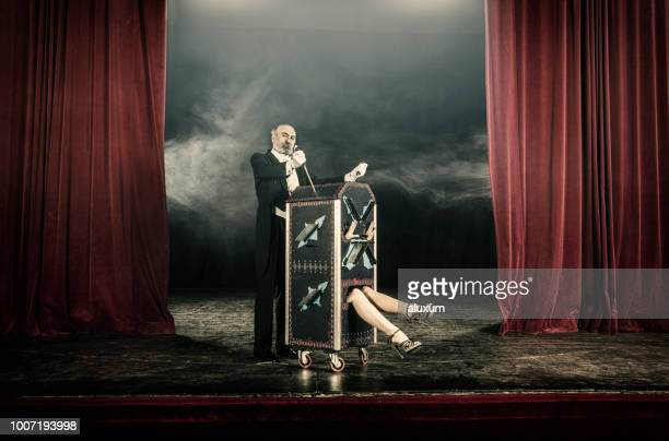 magician inserting swords in box occupied by female assistant - performing arts event stock pictures, royalty-free photos & images