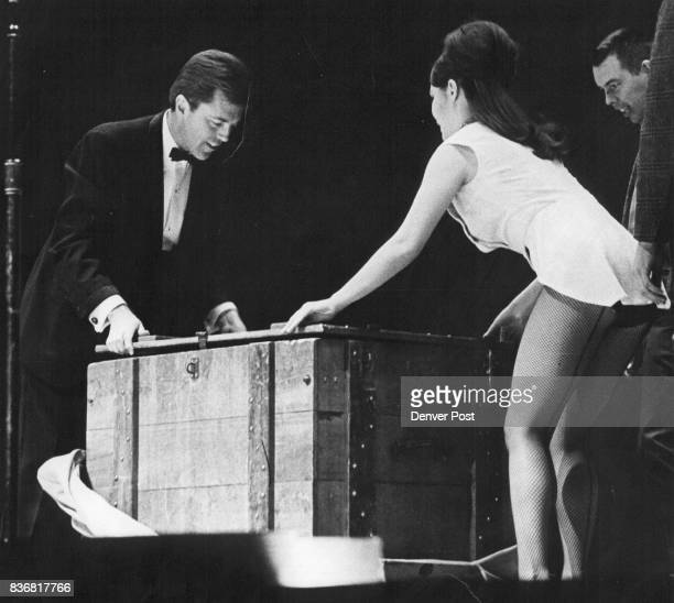 Magician Mark Wilson Left And Assistant Cindy Hull Perform Magic They close up a box containing Wilson's wife who was first put into a black bag...
