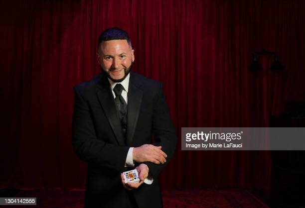magician on stage holding playing cards - comedian stock pictures, royalty-free photos & images