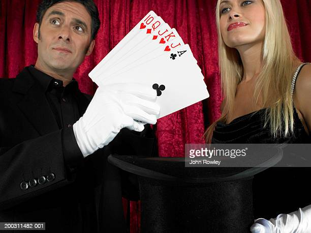 Magician performing card trick with female assistant