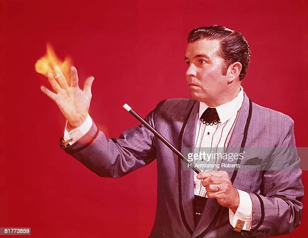 Magician performing illusion, setting hand on fire with magic wand. (Photo by H. Armstrong Roberts/Retrofile/Getty Images)