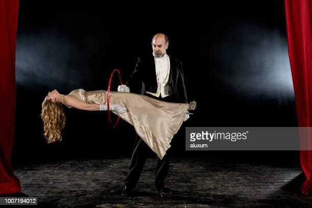 magier, die durchführung von levitation trick auf der bühne - zauberer darstellender künstler stock-fotos und bilder