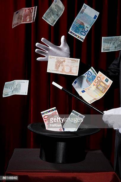 a magician performing magic by making money come out of a hat - five euro banknote stock photos and pictures