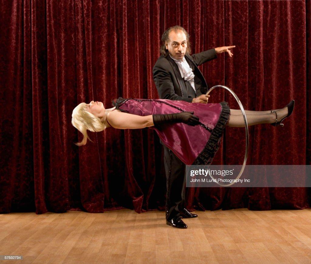 Magician Putting Ring Around Levitating Woman ストックフォト