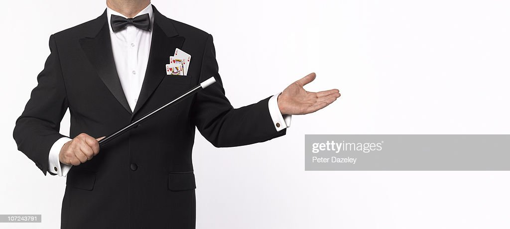 Magician with playing cards and wand : Stock Photo