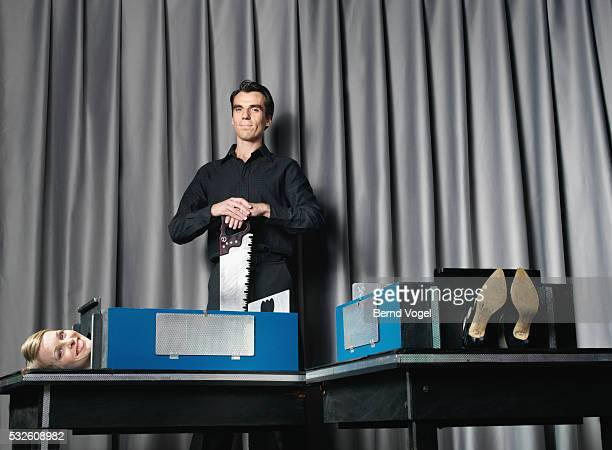magician with saw and his assistant during performance - magician photos et images de collection