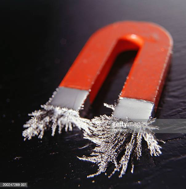 magnet attracting iron filings, elevated view - iron filings stock pictures, royalty-free photos & images