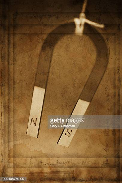 magnet hanging from string (digital composite) - horseshoe magnet stock pictures, royalty-free photos & images
