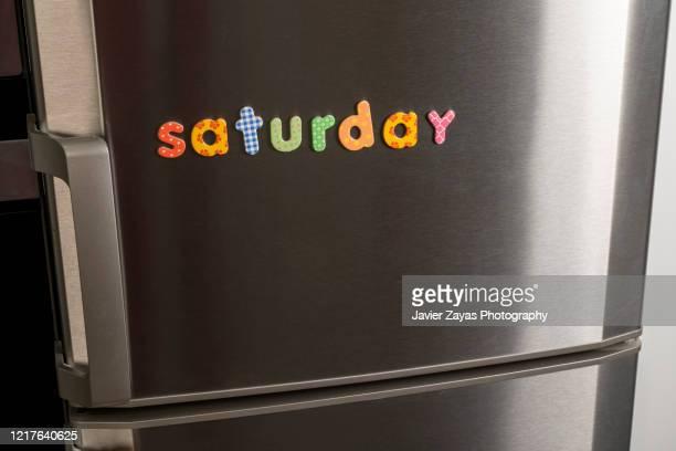 """magnetic letters forming the word """"saturday"""" - sábado fotografías e imágenes de stock"""