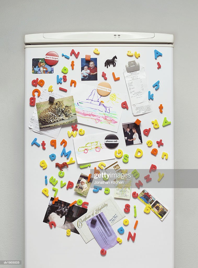 Magnets, Paintings and Photographs on a Fridge Door : Stock Photo
