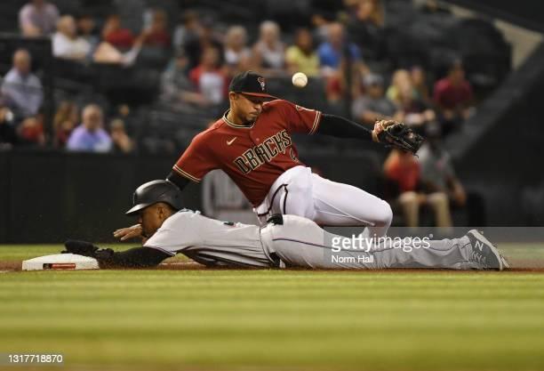 Magneuris Sierra of the Miami Marlins advances safely to third base on a fly ball by Miguel Rojas as Eduardo Escobar of the Arizona Diamondbacks...