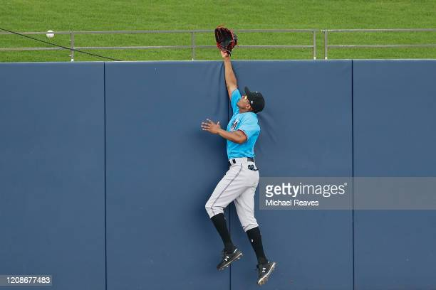 Magneuris Sierra of the Miami Marlins can't catch a home run hit by the Houston Astros during the sixth inning of a Grapefruit League spring training...