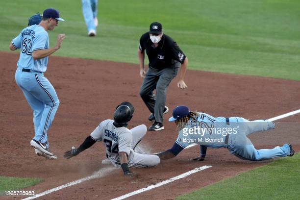 Magneuris Sierra of the Miami Marlins slides into first base as Vladimir Guerrero Jr. #27 of the Toronto Blue Jays tags him during the third inning...