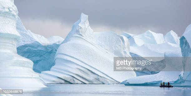 magnificent icebergs with zodiac boat. - poolklimaat stockfoto's en -beelden