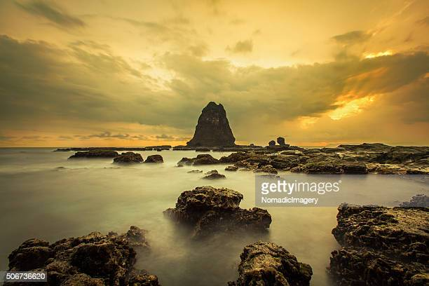 Magnificent Papuma Rock rising out of the sea at sunset