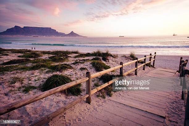 A magnificent view of a sunset unfolds over a wooden boardwalk that leads onto a sandy beach overlooking Table Mountain with a beautiful sun setting over Table Bay, Tableview, Cape Town, Western Cape Province, South Africa.