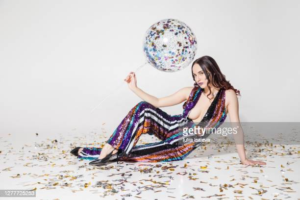 magnificent young woman in glossy striped overall with balloon among colorful confetti - beautiful women breast stock pictures, royalty-free photos & images