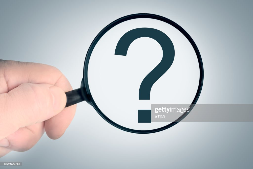 Magnifier in a man hand, question mark on a blue background. : Stock Photo