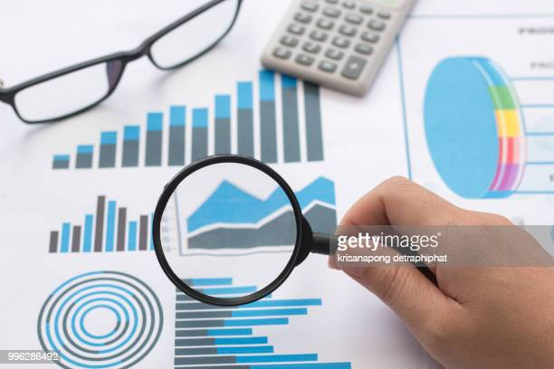 Magnifier with chart,Close-up Of Person's Hand Holding Magnifying Glass Over Graph,